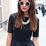 Circle shades and a statement necklace pop against black peplum.