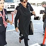 Halle's travel style included slim black jeans, black pumps, a draped black coat, and a black leather tote. It's safe to say Halle likes black!
