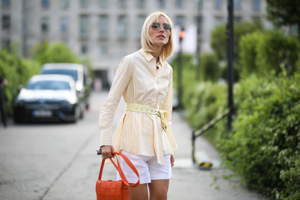 For a pop of color, style a belted blazer with shorts and a bright orange Bottega bag.