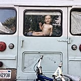 The back of the bus, and a toddler peeping through the window!