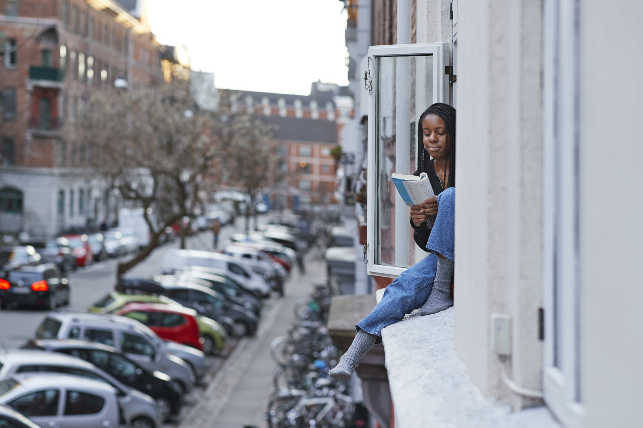 Young woman reading book in apartment window during COVID-19 isolation
