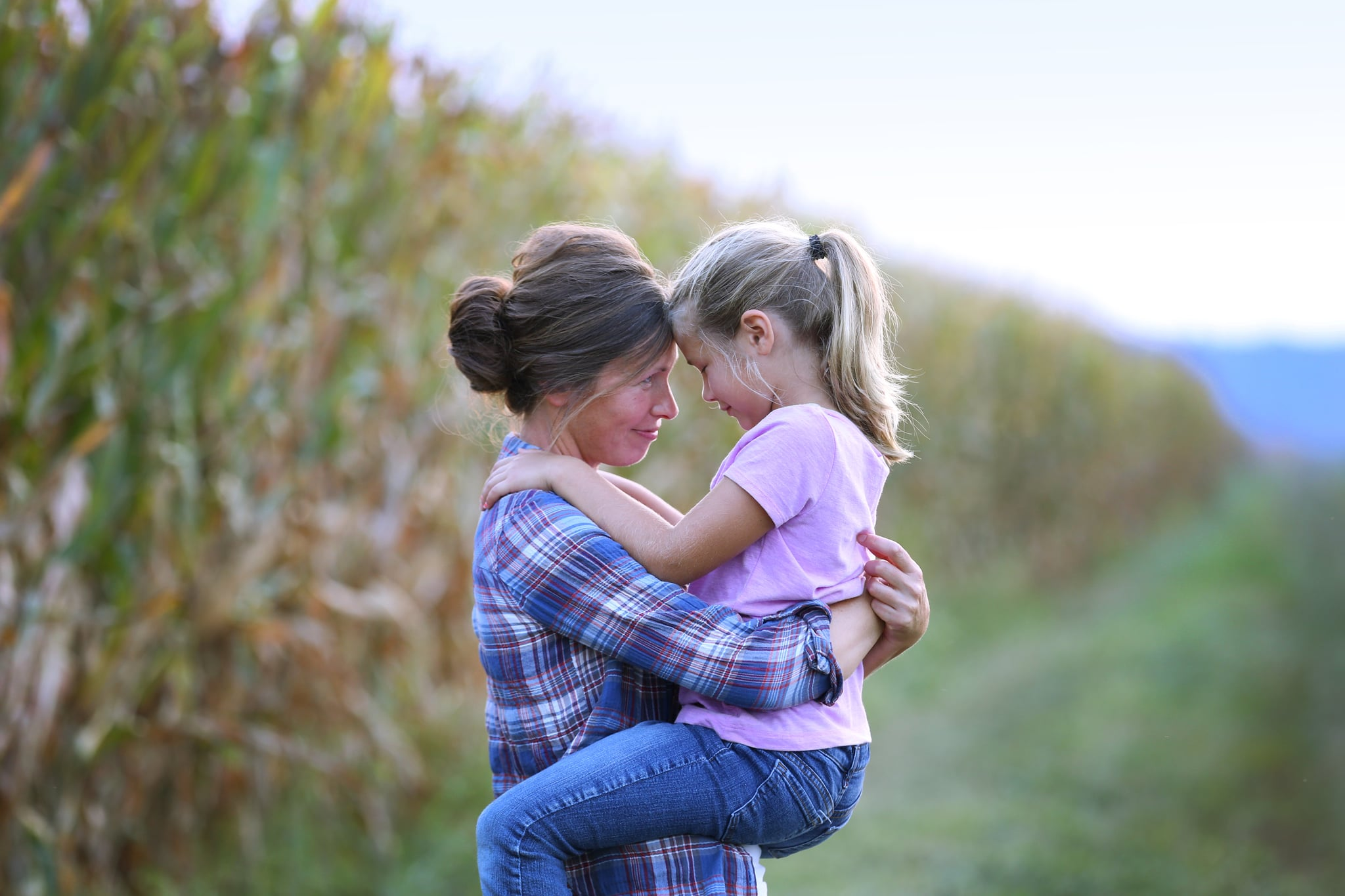 An Iowa farm mother hugs her young daughter while standing next to a field of corn.