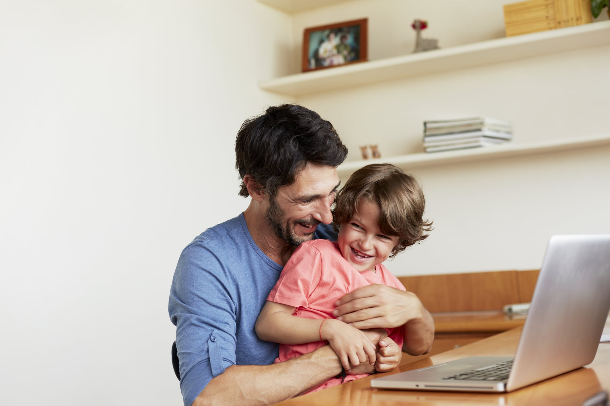 Happy father tickling son at laptop table in house