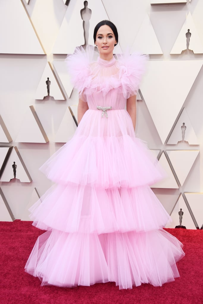 When Kacey Musgraves glided onto the 2019 Oscars red carpet on Feb. 24, I saw visions of Glinda the Good Witch immediately. The cotton candy pink! The tulle! The tiers! The illusion sleeves! I'm surprised the 30-year-old singer and recent Grammy winner didn't arrive to the show in a bubble. Kacey kept the rest of her outfit relatively understated, opting for diamond stud earrings and a metallic clutch.  She helped to introduce a musical performance during the show, so I got even more glimpses of her stunning gown. Ahead, see more photos of Kacey's delicate look.      Related:                                                                                                           These Oscars Gowns Are So Damn Sexy, We Don't Know What to Do With Ourselves