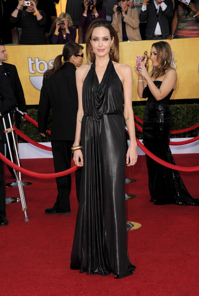 Angelina Jolie was smoking hot in a black, liquidy metallic Jenny Packham halter gown at 2012 SAG Awards. To top it off, Angelina wore oversize, gold-and-black vintage-inspired earrings, a gold bangle cuff, and a black envelope clutch.
