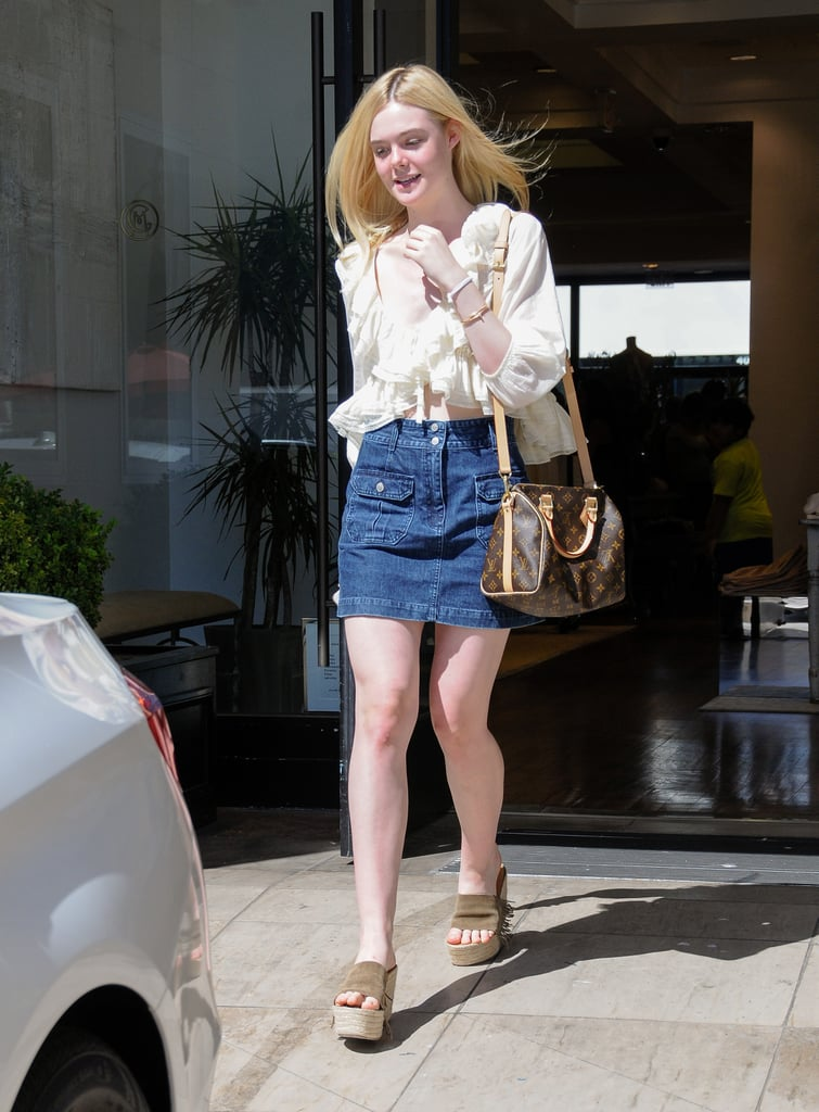 Elle paired her denim mini with a cream ruffled blouse and Louis Vuitton purse.