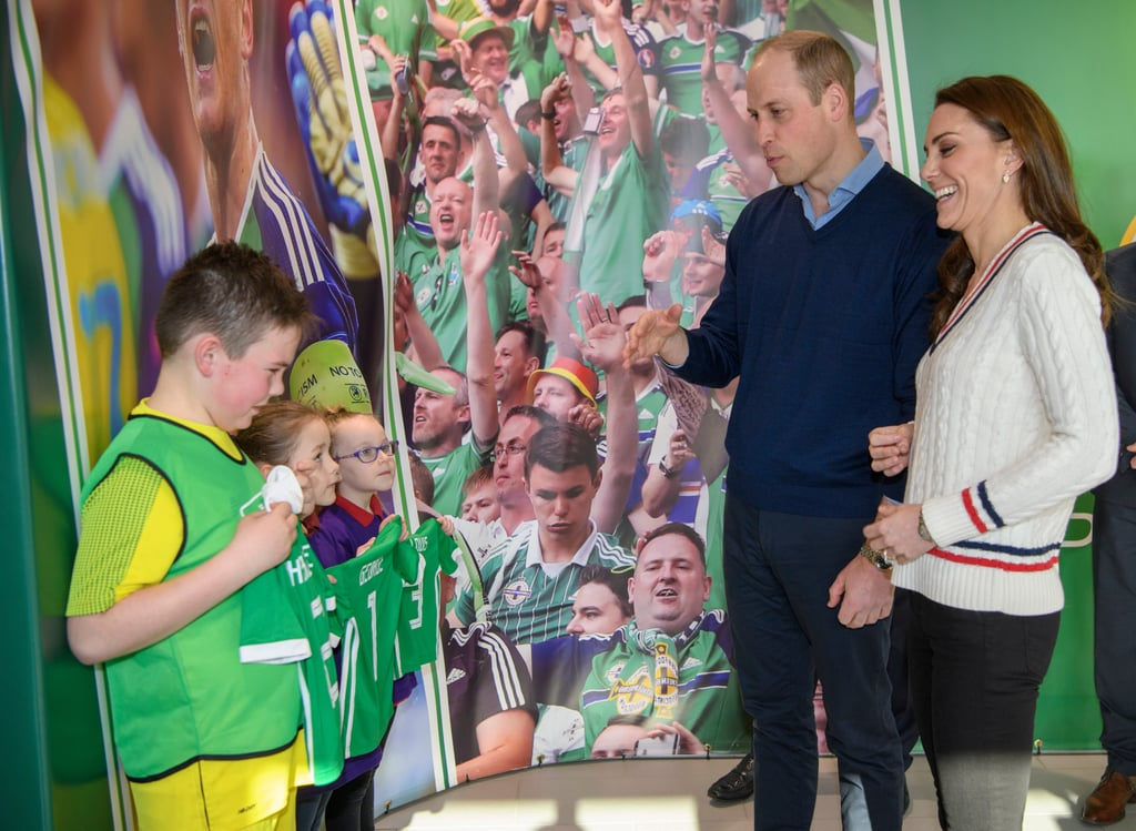 "Kate Middleton and Prince William made a surprise trip to Northern Ireland on Wednesday, but they also received a surprise of their own when they arrived. During their stop at Belfast's National Stadium, the royal couple were gifted some special souvenirs for their kids, Prince George, Princess Charlotte, and Prince Louis: custom soccer jerseys! The jerseys were in the traditional Irish Football Association green and white colors, and George's had the number one on the back, while Charlotte's and Louis's had the numbers two and three, respectively.  Despite showing off her impressive soccer skills, Kate reportedly told The Telegraph that George says they're ""rubbish."" ""I should have picked up some tips from George,"" she added. Will and Kate's two-day trip aims to ""celebrate the young people of Northern Ireland"" and includes stops in Belfast, Fermanagh, and Ballymena.      Related:                                                                                                           28 Pictures of Kate Middleton With Her Young Royal Admirers"