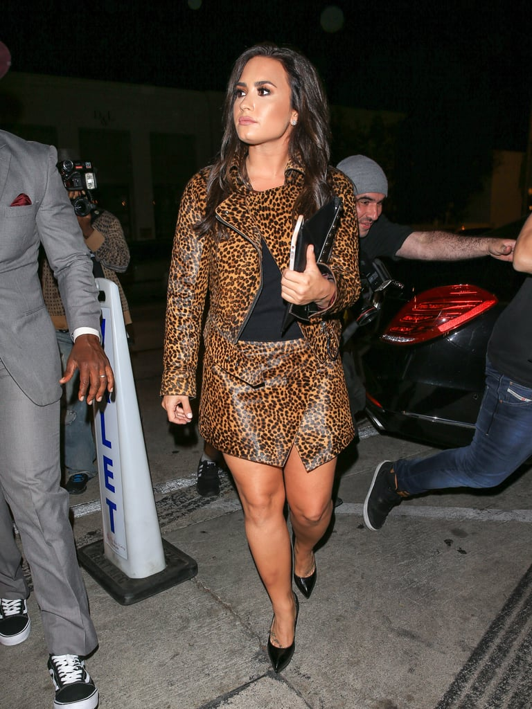 """Mere days after going blond, Demi Lovato went back to brown and turned heads in a fun outfit choice while out in Los Angeles. The """"Body Say"""" singer confidently rocked an animal-print skirt suit that showed off her toned legs and complemented her new hair color. Demi paired the suit simply with black pumps and a tucked-in blouse, making for an effortlessly chic look that could work for the office (no, seriously) or even a night out. Keep scrolling to see more pictures of Demi's outfit in action, then relive her enviable style evolution from the beginning of her career to now."""