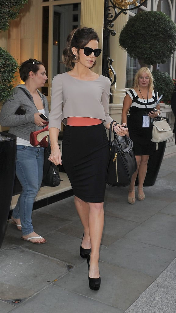 While strutting her svelte stuff in London, Kate sported a chic colorblock Paule Ka look: gray cropped top, black pencil skirt, coral belt, black suede platform Brian Atwood pumps ($754), these Alexander McQueen bag ($2,995).