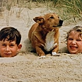 A young Prince Charles and Princess Anne got silly in the sand with one of the queen's Corgis in 1957.