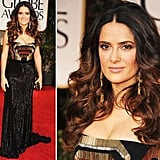 Salma Hayek channeled an ultra-sexy glow on the red carpet tonight. Her art deco-inspired black and gold strapless Gucci Premiere gown looked amazing against her bronzed skin. She chose gold vintage drop earrings and a black satin clutch as her go-to chic accessories.