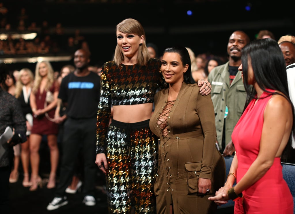 As Kanye West confused the world with his VMAs acceptance speech on Sunday, there stood Taylor Swift and Kim Kardashian in the front row, arms around each other, smiles on their faces. The pair watched as Kanye talked about everything from the importance of ideas to his 2020 presidential run, which actually made Taylor's jaw drop. Keep reading to see some of their hilarious reactions to Kanye's confusing speech, then check out the funny moment Kanye shared with Taylor as she presented him with the Michael Jackson Video Vanguard Award.