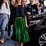 With a pleated skirt in a gorgeous emerald color, Olivia needed little else to dress up this look. She stuck to cat-eye shades and heeled sandals.