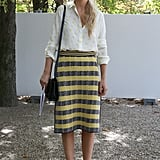 A tweedy skirt and a silk blouse are united by a sweet lemon hue.
