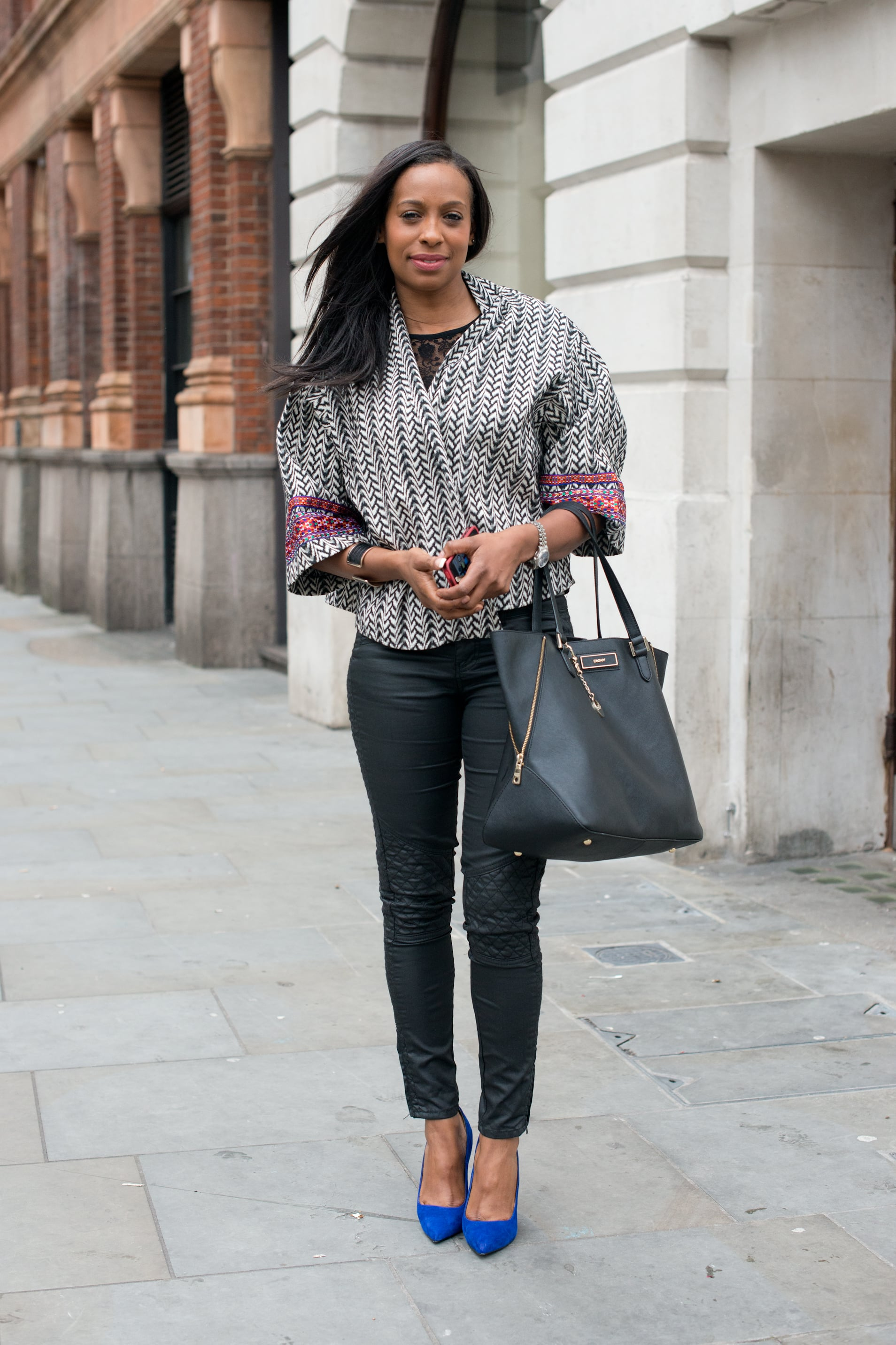 An eclectic print and blue suede heels brightened up her black pants and tote.