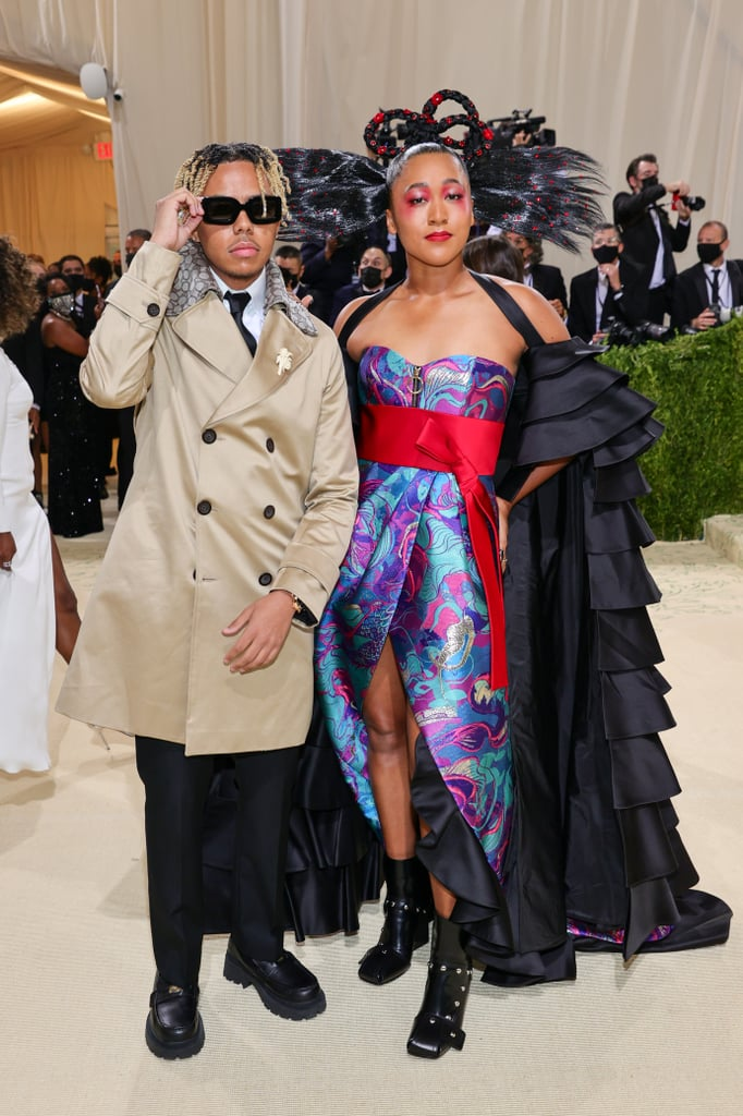 """And the award for prom queen and king of the Met Gala goes to Naomi Osaka and Cordae! On Monday night, the tennis player and the rapper made their red carpet debut as a couple at the 2021 Met Gala and looked cooler than ever. Although Naomi and Cordae have been dating since 2019, they keep their relationship relatively private, giving us glimpses of their romantic gestures and couple vacations on social media. And for Naomi's big night, Cordae was right by her side.  Naomi was one of the cochairs for the 2021 Met Gala with Amanda Gorman, Timothée Chalamet, and Billie Eilish. For the theme """"In America: A Lexicon of Fashion,"""" Naomi wore a gorgeous Louis Vuitton dress designed by Nicolas Ghesquière and her big sister, Mari Osaka. Cordae looked handsome as ever in custom Coach. Check out photos from their red carpet debut at the Met Gala ahead.      Related:                                                                                                           61 Memorable PDA Moments From Met Galas Past"""