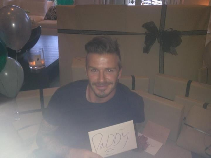 """David Beckham is 37 today, and his family pulled out all the stops! His sons cooked him a semitraditional English breakfast of eggs, bacon, and sausage. It was then time for David to open his presents, which was no small task. David shared another image of himself surrounded by presents, with a Jo Malone candle burning in the background. All the presents were even wrapped the same! The largest gift turned out to be a framed Magic Johnson Lakers jersey, which David dubbed the """"best birthday present ever!"""" It was an appropriate gift for basketball superfan David. In fact, last night, he and Victoria Beckham got a jump on the celebrating as they watched the Lakers beat the Nuggets with his mom, Sandra, and sister Joanne. Victoria and David even appeared on the Kiss Cam! David was appreciative of all the love. He wrote on his Facebook wall, """"Thank you to my amazing family for making my birthday so special!"""""""