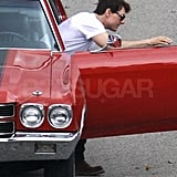 Tom Cruise hopped out of a red sports car.