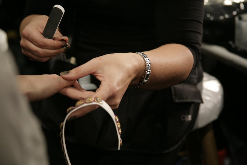 A manicurist applies the retro-meets-modern nails to a model's fingers.  Photo: Megan Holmes