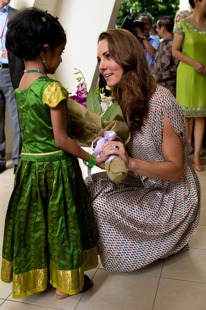 She knelt down to accept flowers from a little girl in traditional Indian attire during a September 2012 stop in Singapore.