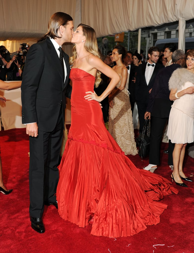 "Gisele Bundchen didn't look worried about her perfect makeup getting messed up by a kiss from her husband, Tom Brady, on the red carpet at tonight's Met Gala in NYC. The supermodel was decked out in an exquisite Alexander McQueen, paying fitting homage to the man of the night. The Costume Institute gala's theme for the year is Alexander McQueen: Savage Beauty, and she made a statement in the very dramatic gown amid the star-studded arrivals. Tom Brady and Gisele Bunchen were sexy at the 2010 Met Gala, and they were once again among tons of other hot couples, including Orlando Bloom and Miranda Kerr and Joshua Jackson and Diane Kruger. Tom also made a stylish statement of his own by slicking back his hair. Gisele even spoke about Tom's locks, saying of his 'do, ""That's his choice! He can do whatever he wants because I'll love it no matter what. Short, long, red, whatever! It's all good!"" What do you think of Tom and Gisele's look?"