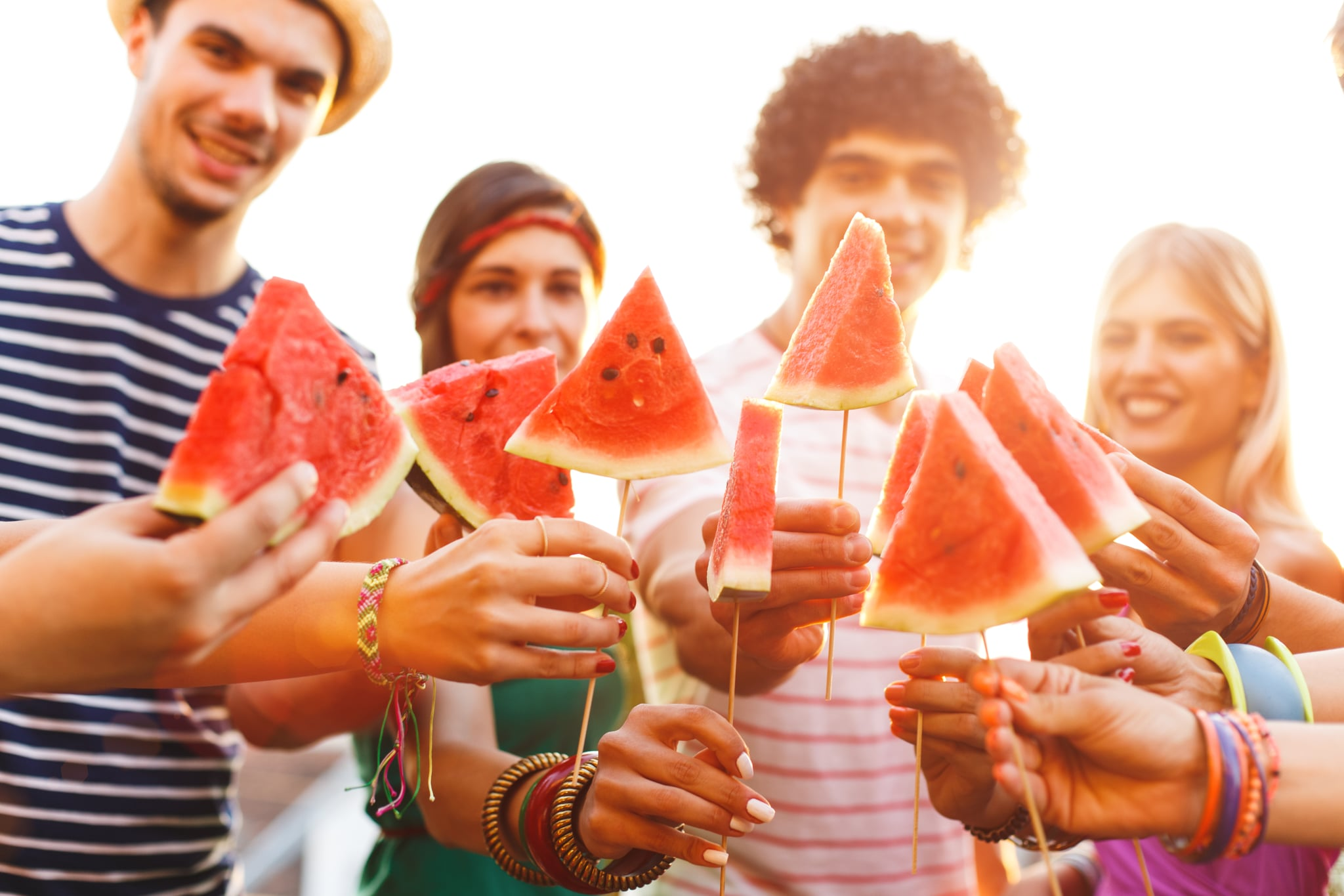 Group of young friends holding watermelon slices on a wooden stick on rooftop party, having fun, toasting.