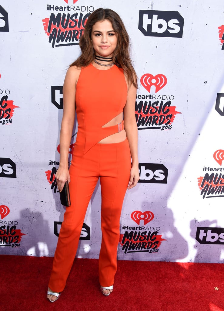 By adding this layered choker, Selena Gomez took her fun orange jumpsuit to the next level.