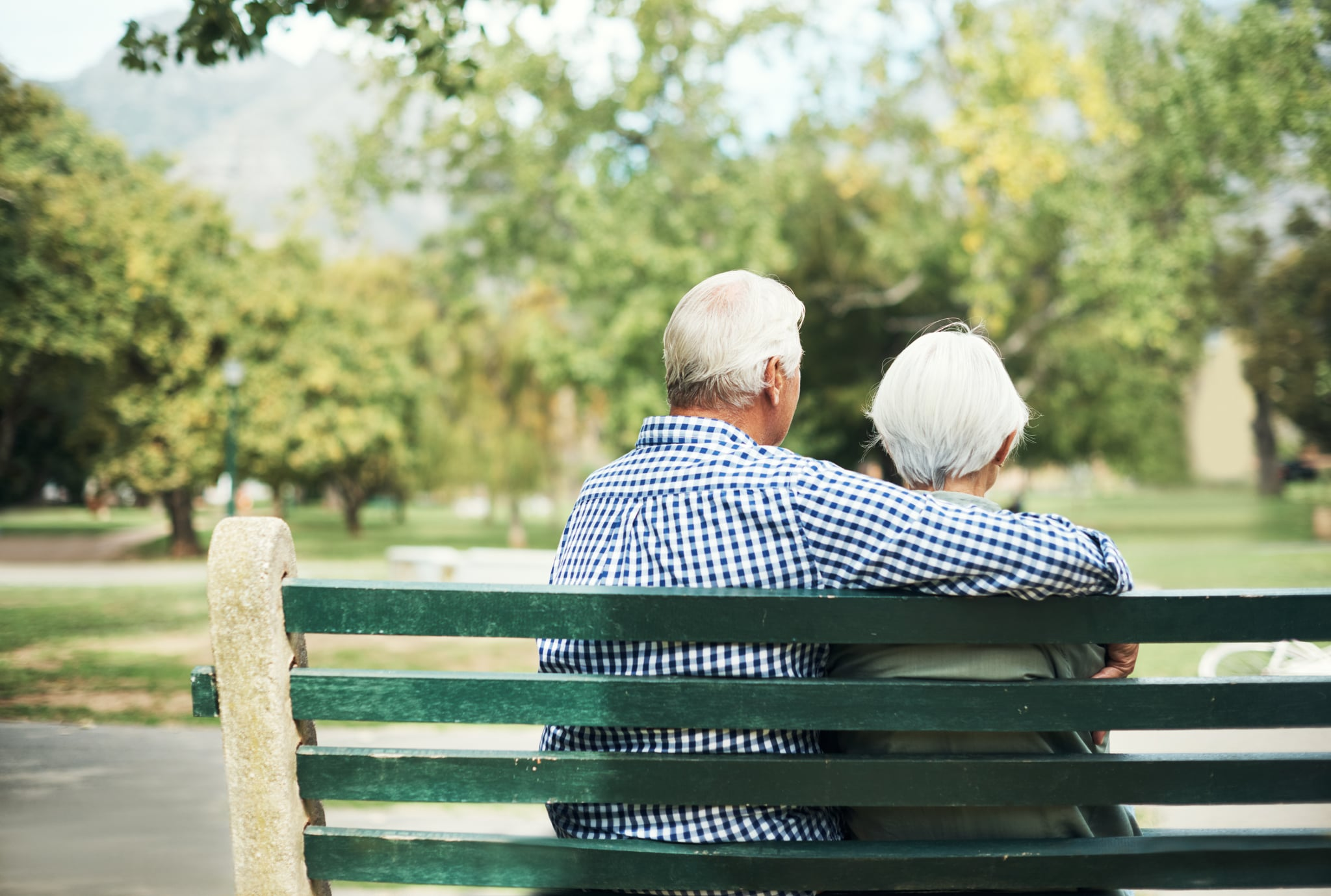 Rearview shot of a senior couple relaxing together on a park bench