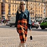 A plaid pencil skirt and plaid button-down might feel busy, but stark white boots temper the busy prints