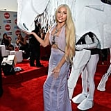 "In true Lady Gaga fashion, the avant-garde star accessorized her lavender cutout Versace gown with a white ""human horse"" at the 2013 American Music Awards."