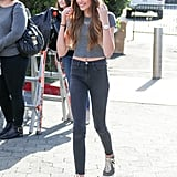 "Kaia had her own spin on the ""groutfit"" while on the set of Extra with Cindy Crawford. She paired high-waisted gray jeasn with a gray crop top and gray Nike high tops!"