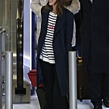 """The centerpiece of Jessica Alba's très chic travel style was her striped and sequined """"Je T'aime"""" sweater, which she finished with D'Orsay flats and a classic coat."""