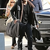 Orlando Bloom carried his snowboard to a plane at LAX.