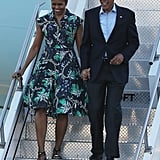 Michelle disembarked from Air Force One in Mary Katrantzou's lightweight  button-down dress back in June. We love how her gold-plated, strappy black sandals and hoop earrings play up the yellow tones of the tropical pattern.