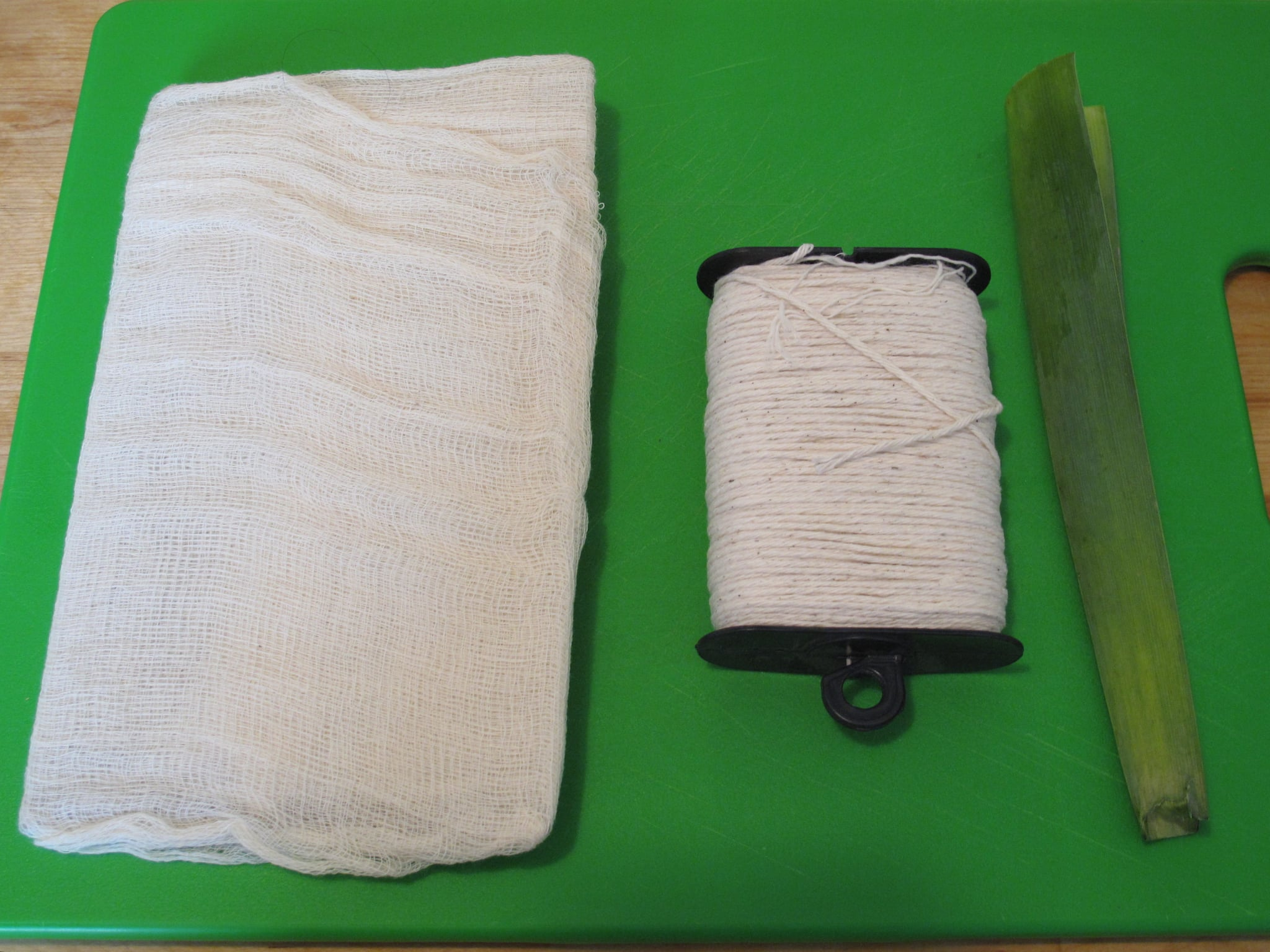 The string will be wrapped around two leek leaves; however, if you have cheesecloth on hand, you can create a pouch with that instead, and secure with kitchen twine.