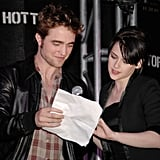 Robert Pattinson and Kristen Stewart helped each other while speaking at a Hot Topic store in LA during the New Moon press tour in November 2009.