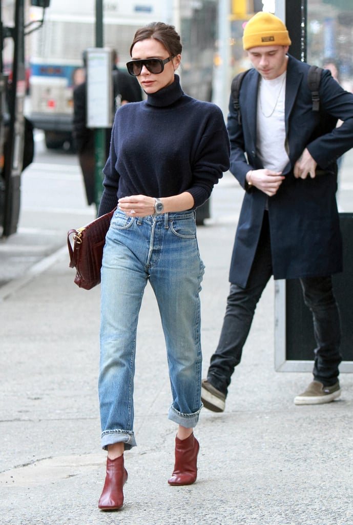 Wearing a navy turtleneck sweater, boyfriend jeans, and ankle boots.