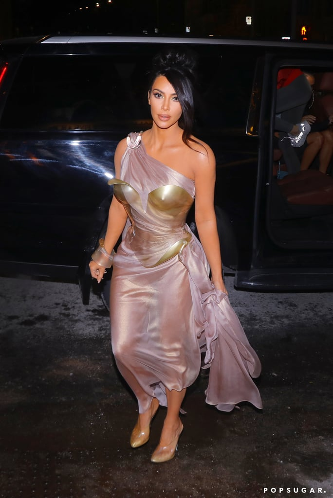 Kim Kardashian is going full Mugler, folks. She celebrated the French designer at the Thierry Mugler: Couturissime museum exhibition in Montreal on Feb. 25 and wore not one but two of his vintage outfits. Channeling her inner goddess, Kim first opted for a sheer one-shoulder gold and lavender number, which draped across her body and included a corset that could double as body armor. She paired the daring vintage look with her signature clear heels and minimal accessories. Shortly after giving off her golden glow, Kim changed into another unique outfit. This time, she picked a low-cut strapless scalloped gown with sleek modern arm cuffs.  Perhaps this exhibition opening is why Kim's been gravitating toward Mugler's work lately. Earlier this month, she kept fans on edge with her risky cutout gown and snakeskin dress on two different occasions. Mugler is known for his out-of-the-box designs, and Kim doesn't shy away from a stylish challenge, so they're practically a match made in heaven.  Check out glimpses of both her looks ahead.       Related:                                                                                                           I'm Holding in My Breath Just Looking at Kim Kardashian's Snakeskin Dress