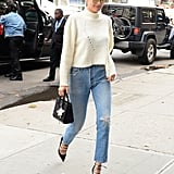 Accenting her cream cropped knit and high-waisted jeans with strappy shoes and a Saint Laurent bag.