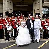 A freshly married couple posed with torchbearer Edwin Wesolowski in front of the Band of the Royal Fusileers in Bury, England.