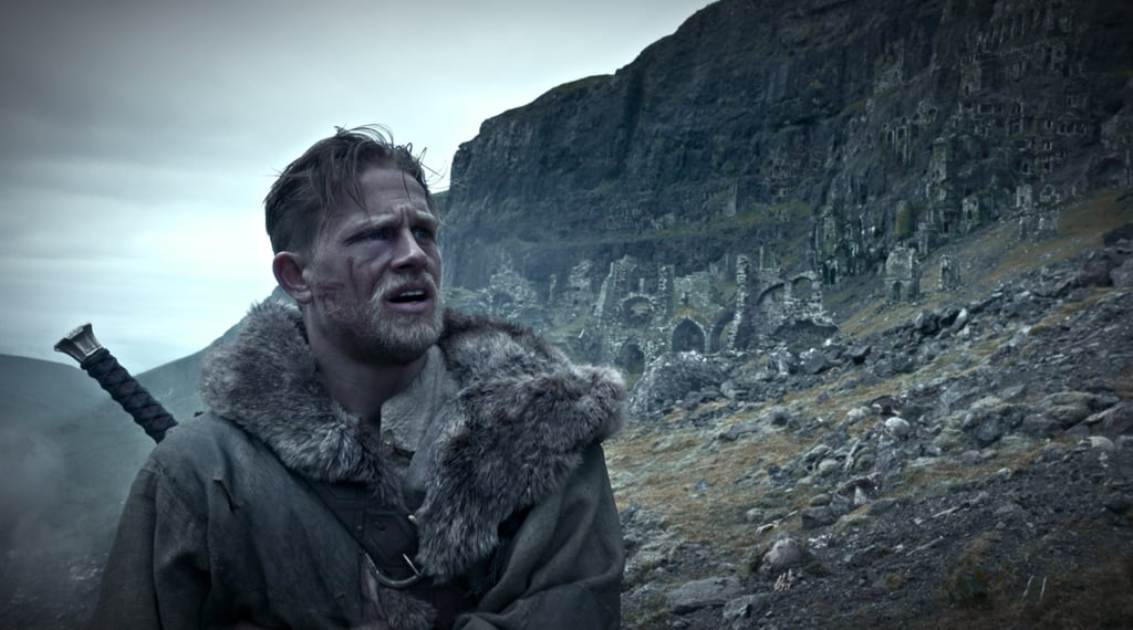 While King Arthur: Legend of the Sword isn't out until March 2017, the first look at Guy Ritchie's upcoming film is finally here. Not only did Warner Bros. release the first full-length trailer at Comic-Con on Saturday, but they also gave us another sneak peek at the film with these action-packed stills. The images show Jude Law as Vortigern and Charlie Hunnam as King Arthur, and if that's not enough to get you excited, perhaps this cover of Charlie handling his sword will do the trick.