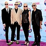 Gwen Stefani posed with her crew wearing a black leather top, trousers, ankle strap sandals, and cat-eye sunglasses.