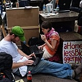 A couple sit on their computers in the streets of NYC.