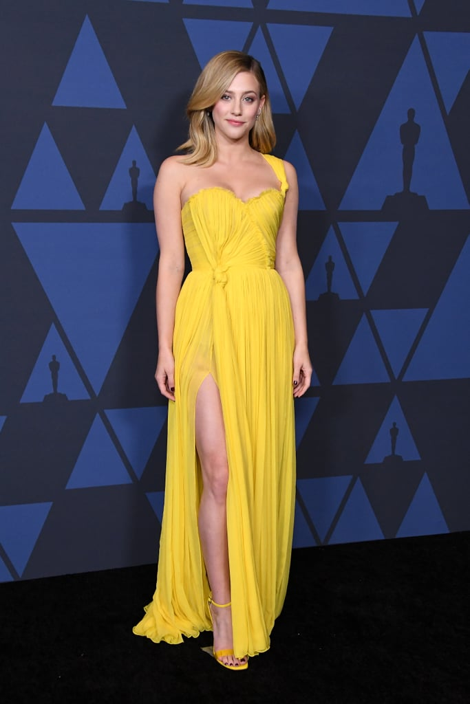 "Lili Reinhart seems to be staying true to her feminine style. The Riverdale actress attended the 2019 Governors Awards in Los Angeles on Sunday wearing a draped Oscar de la Renta gown, which has been described by the brand as being mimosa-colored. (Anyone else suddenly craving eggs Benedict? No?) Lili paired the vibrant gown with matching ankle-strap Loriblu sandals and diamond jewelry by Messika.  Now, are you ready for a pretty surprising revelation? Lili's entire ultraelegent look — that's hair, makeup, nails, everything! — took just one hour to achieve. In a post she shared to Instagram following the award ceremony, Lili wrote, ""My glam team gets an honorary Oscar for getting me ready in 1 hour.""  Also in attendance was Lili's Hustlers costar Jennifer Lopez, who wore a satin Reem Acra column dress in a similar golden hue. If these dresses are any indication, we're looking forward to the many award season events and red carpets that lie ahead.       Related:                                                                                                           Lili Reinhart on Working With ""Badass Women"" in Hustlers and on Riverdale: ""I'm Very Grateful"""