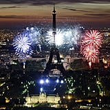 Bastille Day fireworks light up the sky in blue, white, and red.