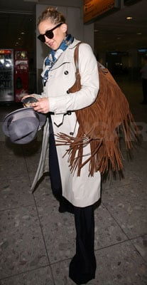 Kate Hudson in Trench Coat, Fringe Bag, and Silk Scarf at Heathrow Airport
