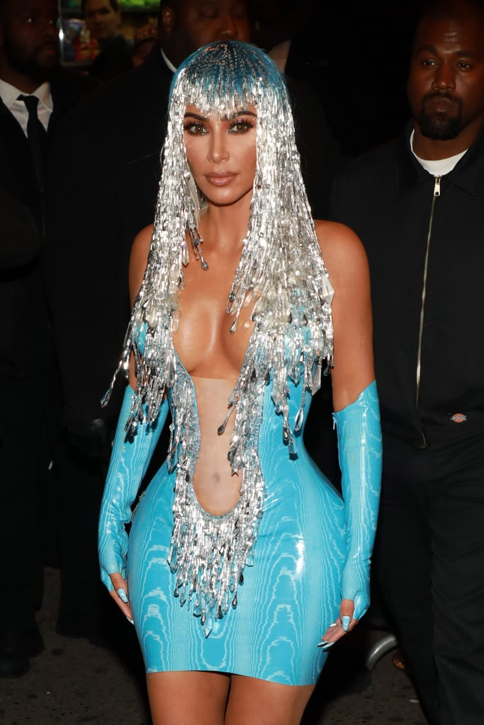 "For most Met Gala attendees, the afterparties are an excuse to slip into something a little more comfortable. Not so for Kardashian, who used the gala's official afterparty as an excuse to show off an even more outrageous and revealing design than the one she wore on the red carpet. After arriving at the gala in a Thierry Mugler dress that brought a whole new meaning to the phrase ""wet look,"" Kim kept up the latex theme as she swapped her nude dress for an even shorter and tighter design. Her skintight blue minidress featured a fringed and beaded neckline that plunged right down to the navel, and it came with matching fingerless gloves and calf boots in the same bright hue. She topped the look with a long, silver beaded wig, which conjured up visions of Cher in the 1970s. We know that Kim's a fan of the singer — she dressed up as her for Halloween in 2017 — and Cher actually performed a trio of songs during the Met Gala, so it's no surprise Kim decided to pay homage once again. Keep reading to see Kim's look from all angles and to see the Cher look we think she was channeling."