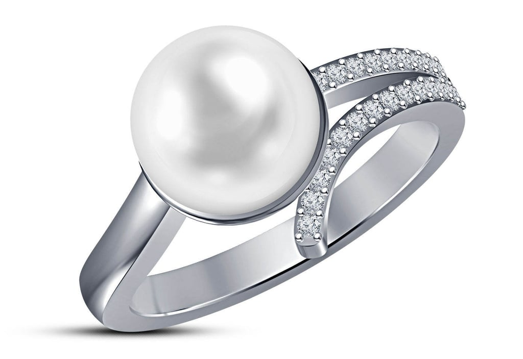 A pearl sits center on this silver engagement ring ($698) with 18 round diamonds.