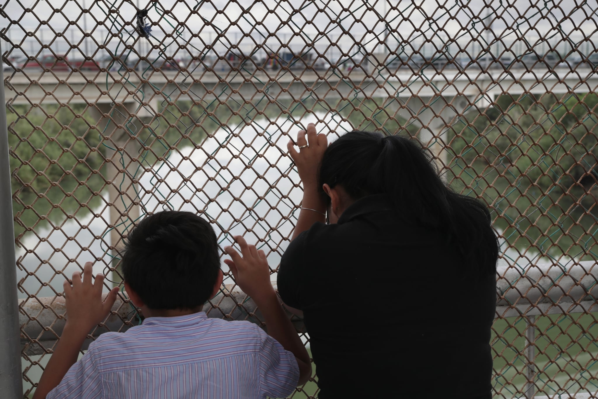 HIDALGO, TX - NOVEMBER 04:  Nicaraguan asylum seekers wait for entry into the United States while on the international bridge on November 4, 2018 in Hidalgo, Texas. President Trump ordered U.S. troops to border areas days before the midterm elections and weeks before the possible arrival of a caravan of immigrants from Central America.  (Photo by John Moore/Getty Images)