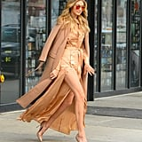 Going for the golden girl look, Gigi wore a satin-colored Self-Portrait dress with a beige trench draped over her shoulders.